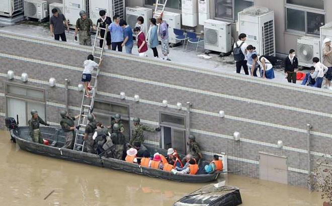 Các lực lượng phòng vệ đưa người dân ra khỏi vùng lụt tại tỉnh Okayama. Ảnh: Kyodo.